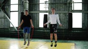 Νέοι μπόξερ στα περιστασιακά ενδύματα που πηδούν χρησιμοποιώντας ένα σχοινί άλματος θερμαίνοντας στην στούντιο-γυμναστική εγκιβωτ απόθεμα βίντεο