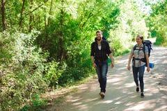 Νέοι οδοιπόροι ζευγών στο δασικούς αθλητή και τη γυναίκα με τα σακίδια πλάτης στο δρόμο στη φύση στοκ εικόνες
