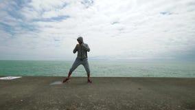 Νέος αθλητικός τύπος, που συμμετέχεται ενεργά στον αθλητισμό, crossfit, στην ακτή της λίμνης κίνηση αργή φιλμ μικρού μήκους