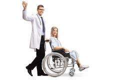 Νέος αρσενικός γιατρός που κυματίζει και που ωθεί έναν θηλυκό ασθενή σε μια αναπηρική καρέκλα στοκ φωτογραφίες