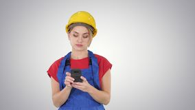 Νέος επαγγελματικός θηλυκός ανάδοχος που φορά το σκληρό καπέλο Texting με το τηλέφωνο κυττάρων στο υπόβαθρο κλίσης φιλμ μικρού μήκους