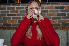Νέος καφές κατανάλωσης γυναικών σε έναν καφέ στοκ εικόνες με δικαίωμα ελεύθερης χρήσης