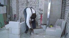 Νέος καυκάσιος οικοδόμος που βάζει το κονίαμα στις πλευρές του αερισμένου τσιμεντένιου ογκόλιθου απόθεμα βίντεο
