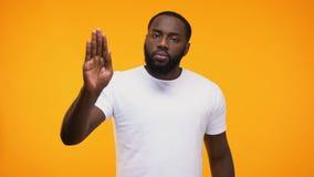 Νέος μαύρος τύπος που παρουσιάζει χειρονομία στάσεων με το φοίνικα, που απομονώνεται στο κίτρινο υπόβαθρο φιλμ μικρού μήκους