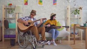 Νέος με ειδικές ανάγκες άνδρας σε έναν κιθαρίστα αναπηρικών καρεκλών και νέες κιθάρες παιχνιδιού γυναικών απόθεμα βίντεο