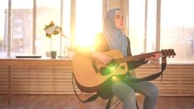 Νέος μουσουλμανικός μουσικός γυναικών στην κιθάρα παιχνιδιού hijab στο σύγχρονο διαμέρισμα απόθεμα βίντεο