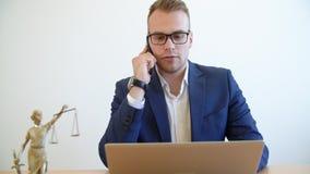 Νέος δικηγόρος που μιλά το κινητό τηλέφωνο και που εργάζεται στο lap-top στον πίνακα στο δικηγορικό γραφείο απόθεμα βίντεο