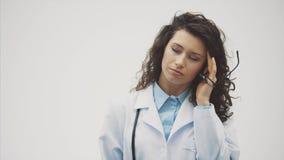 Νέος όμορφος γιατρός brunette σε ένα γκρίζο υπόβαθρο Φθορά των ομοιόμορφων ιατρικών στολών Σε ένα γκρίζο βάσανο υποβάθρου απόθεμα βίντεο