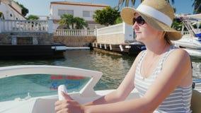 Νέος τουρίστας γυναικών με τα γυαλιά ηλίου που κάθεται στους ελέγχους μιας μικρής βάρκας Κανάλι Empuriarava πανιών στην Ισπανία Έ απόθεμα βίντεο