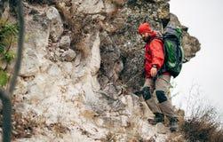 Νέο αρσενικό οδοιπόρων που στα βουνά που φορούν τα κόκκινα ενδύματα που ερευνούν τη νέα θέση Οδοιπορία και ορειβασία ταξιδιωτικών στοκ φωτογραφία με δικαίωμα ελεύθερης χρήσης