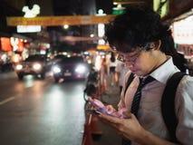 Νέο ασιατικό επιχειρησιακό άτομο που χρησιμοποιεί το κινητό έξυπνο τηλέφωνο στην οδό τη νύχτα Κοινωνικός και Διαδίκτυο της έννοια στοκ εικόνα με δικαίωμα ελεύθερης χρήσης