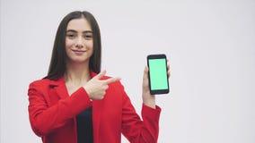 Νέο εξεζητημένο κορίτσι που φορά ένα κόκκινο σακάκι Παραμονές σε ένα γκρίζο υπόβαθρο Κατά τη διάρκεια αυτής της περιόδου, κρατά έ απόθεμα βίντεο
