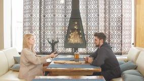 Νέο εύθυμο ζεύγος στα μαλακά μπουρνούζια που κάθεται στον πίνακα με τα φλυτζάνια φιλμ μικρού μήκους