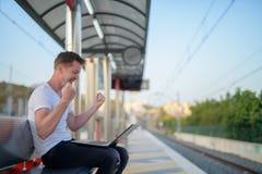Νέο ευτυχές άτομο τουριστών που χρησιμοποιεί το lap-top με την πυγμή που αυξάνεται στο σταθμό τρένου στοκ φωτογραφίες με δικαίωμα ελεύθερης χρήσης