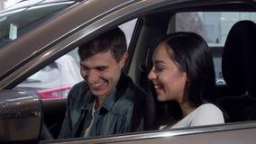 Νέο ευτυχές ζεύγος που επιλέγει το νέο αυτοκίνητο στο σαλόνι αντιπροσώπων απόθεμα βίντεο