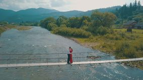 Νέο ζεύγος μαζί στη γέφυρα πέρα από τον ποταμό Θερινός νεφελώδης καιρός Πυροβολισμός από τον αέρα φιλμ μικρού μήκους