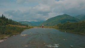 Νέο ζεύγος μαζί στη γέφυρα πέρα από τον ποταμό Θερινός νεφελώδης καιρός Πυροβολισμός από τον αέρα απόθεμα βίντεο