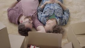 Νέο ζεύγος που βρίσκεται στο πάτωμα με πολλά κιβώτια κοντά στενό σε επάνω Συζήτηση ανδρών και γυναικών, που βρίσκεται στο χνουδωτ απόθεμα βίντεο
