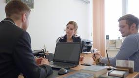 Νέο ζεύγος που συσκέπτεται με τον επαγγελματικό δικηγόρο στο δικηγορικό γραφείο Υπηρεσίες δικηγόρων απόθεμα βίντεο