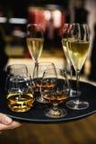 Νέο κομψό άτομο που στέκεται στο εστιατόριο, που κρατά ένα πιάτο με τα ποτήρια του κρασιού και του κονιάκ, ουίσκυ Ύφος ατόμων ` s στοκ εικόνα