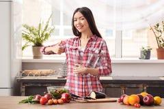 Νέο κορίτσι στον υγιή τρόπο ζωής κουζινών που στέκεται με τα μπουκάλια νερό που ανατρέχουν εύθυμος παρουσιάζοντας αντίχειρας καμε στοκ εικόνα