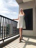 Νέο κορίτσι στο απότομα άσπρο φόρεμα στο μπαλκόνι το καλοκαίρι στοκ εικόνες