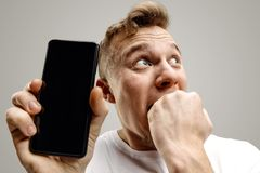 Νέο όμορφο άτομο που παρουσιάζει οθόνη smartphone που απομονώνεται στο γκρίζο υπόβαθρο στον κλονισμό με ένα αιφνιδιαστικό πρόσωπο στοκ φωτογραφίες