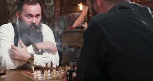 Νέο όμορφο γενειοφόρο σκάκι παιχνιδιού ατόμων με το φίλο του σε ένα μπαρ φιλμ μικρού μήκους