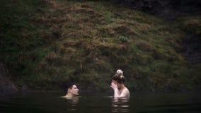 Νέο όμορφο ζεύγος που έχει τη διασκέδαση μαζί κατά τη διάρκεια της κολύμβησης Άνδρας και γυναίκα τις καυτές ανοίξεις στην Ισλανδί απόθεμα βίντεο