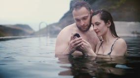 Νέο όμορφο ζεύγος που κολυμπά τις καυτές ανοίξεις στην κοιλάδα βουνών, που φαίνεται φωτογραφίες στο smartphone μαζί στην Ισλανδία απόθεμα βίντεο