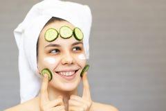 Νέο όμορφο κορίτσι με τις φέτες αγγουριών στο πρόσωπο πέρα από το άσπρο υπόβαθρο Ομορφιά skincare και cosmetology στοκ φωτογραφία με δικαίωμα ελεύθερης χρήσης