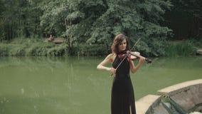 Νέο όμορφο κορίτσι στο μαύρο βιολί παιχνιδιών φορεμάτων που μένει στη γέφυρα υπαίθρια απόθεμα βίντεο
