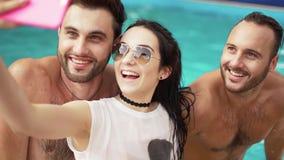Νέο όμορφο κορίτσι που κάνει ένα sephi και που αγκαλιάζει δύο όμορφα άτομά της στα πλαίσια μιας πισίνας απόθεμα βίντεο