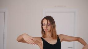 Νέο όμορφο ballerina γυναικών στα γυαλιά που εκπαιδεύουν το χορό στο στούντιο απόθεμα βίντεο