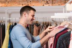Νέο χαμογελώντας άτομο στα ενδύματα στο κατάστημα στοκ φωτογραφία με δικαίωμα ελεύθερης χρήσης