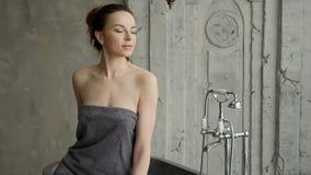Νέο προκλητικό κορίτσι που στέκεται σε μια πετσέτα φιλμ μικρού μήκους