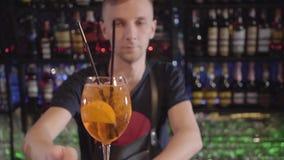Νέο bartender στο εστιατόριο έβαλε ένα γυαλί κρασιού στο φραγμό με το κίτρινα κοκτέιλ και το πορτοκάλι μέσα απόθεμα βίντεο