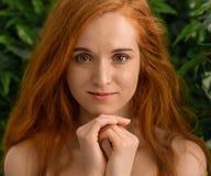 Νέο redhead κορίτσι που εξετάζει τη κάμερα, πράσινο υπόβαθρο φύλλων στοκ φωτογραφία με δικαίωμα ελεύθερης χρήσης