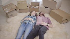 Νέο smilling ζεύγος που βρίσκεται στο πάτωμα με πολλά κιβώτια πλησίον Συζήτηση ανδρών και γυναικών, που βρίσκεται στο χνουδωτό τά απόθεμα βίντεο