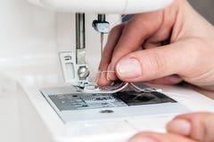 Νήμα και πέρασμα κλωστής σε βελόνα μιας βελόνας ράβοντας μηχανών στοκ φωτογραφία με δικαίωμα ελεύθερης χρήσης