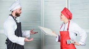 Να εξαργυρώσει επάνω Αρωγός μαγείρων που δίνει το μαγειρεύοντας φύλλο εργασίας στον αρχιμάγειρα Κύριο βιβλίο απολογισμού μαγείρων στοκ εικόνα