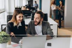 Να εργαστεί μαζί στο πρόγραμμα Δύο νέοι επιχειρησιακοί συνάδελφοι που εργάζονται στον υπολογιστή στοκ εικόνες