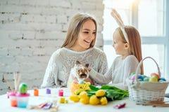 Να προετοιμαστεί για Πάσχα με τη μητέρα μου Η μικρή κόρη με τη μητέρα της κτυπά ένα εγχώριο διακοσμητικό κουνέλι στοκ εικόνες