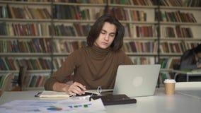Νεαρός άνδρας με μακρυμάλλη κτυπώντας τη συνεδρίαση σημειωματάριων στη βιβλιοθήκη απόθεμα βίντεο