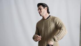 Νεαρός άνδρας που αισθάνεται καυτός στο μήκος σε πόδηα στούντιο φιλμ μικρού μήκους