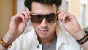 Νεαρός άνδρας που βάζει στα γυαλιά ηλίου που εξετάζουν τη κάμερα απόθεμα βίντεο