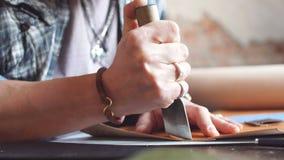 Νεαρός άνδρας που χρησιμοποιεί ένα ειδικό μαχαίρι για να κόψει το δέρμα απόθεμα βίντεο