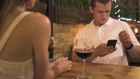 Νεαρός άνδρας που χρησιμοποιεί το κινητό τηλέφωνο ενώ ρομαντική ημερομηνία στον καφέ βραδιού Όμορφο άτομο που εξετάζει smartphone φιλμ μικρού μήκους