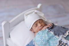 Νεογέννητος ύπνος αγοράκι σε ένα μικροσκοπικό κρεβάτι στοκ φωτογραφία