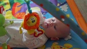 Νεογέννητο παιχνίδι μωρών στη ζωηρόχρωμη γυμναστική μωρών του απόθεμα βίντεο